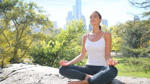 woman meditating on a rock in central park