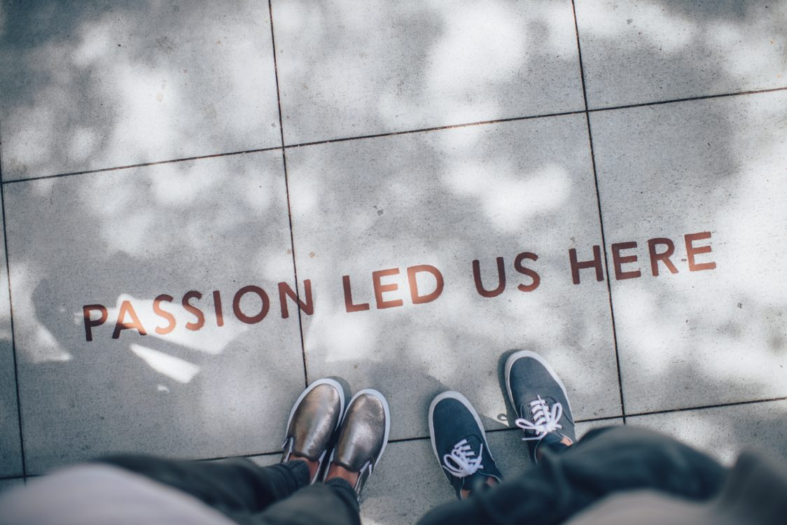"two people standing on a sidewalk next to words ""passion led us here"""