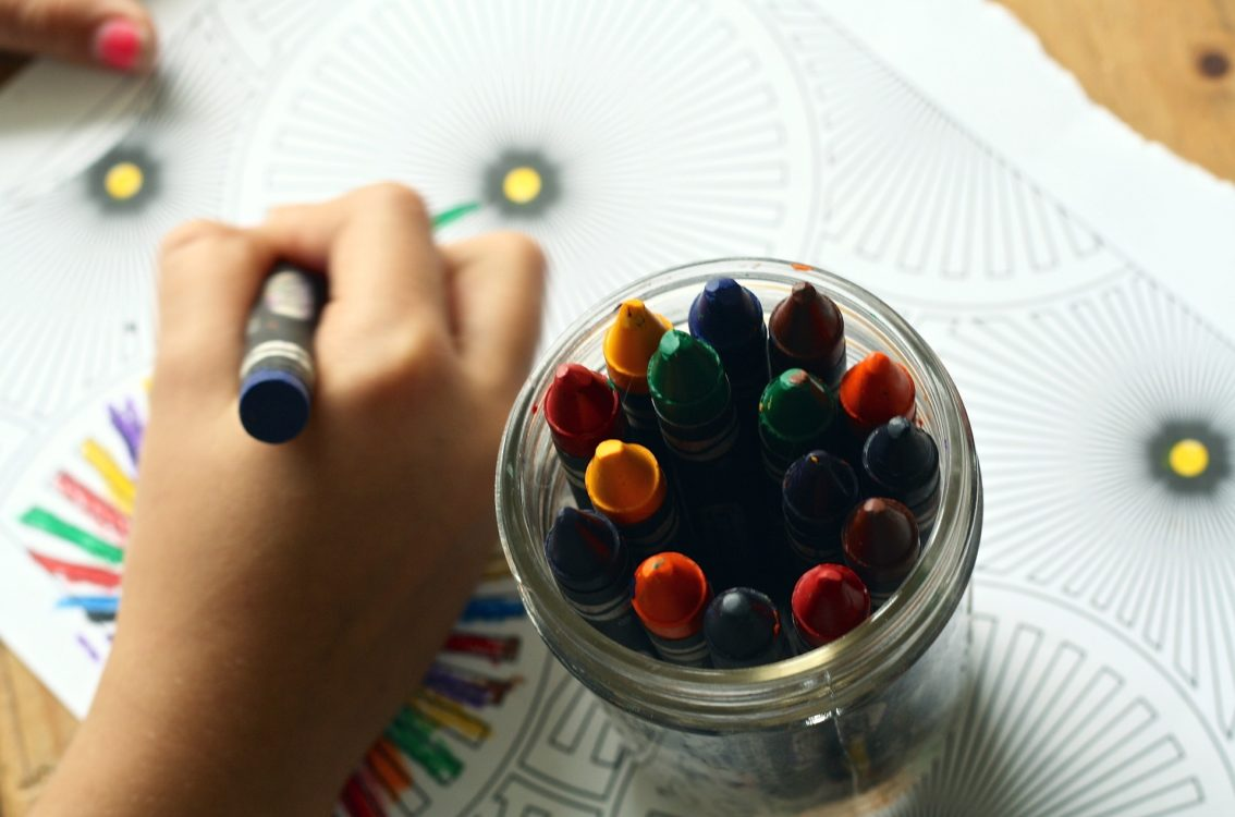 child coloring with crayon