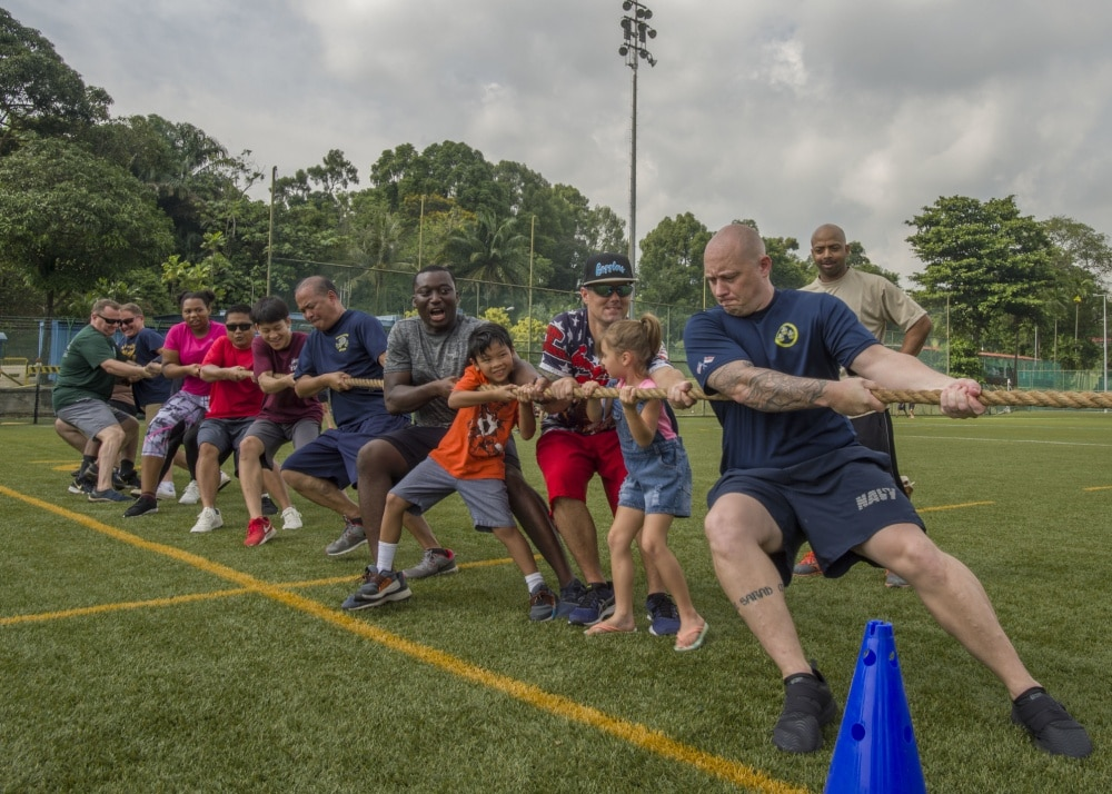 adults playing tug o war on base